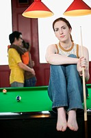 Young Woman Sitting on Billiard Table