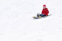 Girl Tobogganing Down Hill