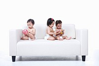 Babies Wearing Dyper On White Sofa With Toys