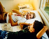Boy and girl phoning on bed