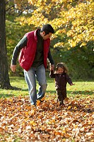 Father and Daughter Running in Leaves in High Park, Toronto, Ontario