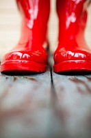 Selective focus of toes of red rainboots. Boots are outside on wooden porch with peeling paint.