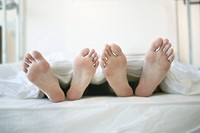 Feet of Couple Relaxing in Bed
