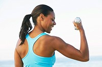 Woman Lifting Weights on Beach