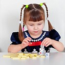 Child playing with small toys at table