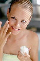 Smiling Woman Applying Facial Cream
