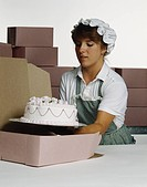 Young woman packing cake in box