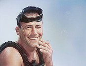Man wearing snorkel smoking cigarette, smiling, portrait