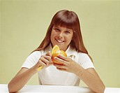 Teenage girl peeling orange, smiling, portrait