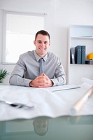 Close up of architect smiling and sitting behind a table