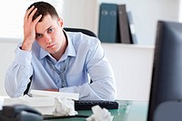 Close up of frustrated young businessman doing his accounting
