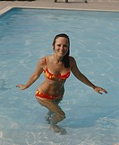 Young woman walking in swimming pool, portrait