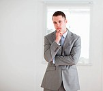 Standing young businessman considering
