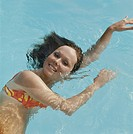 Young woman swimming in pool, smiling, portrait