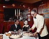 Waiter cutting cake while young women looking up