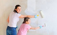Happy Mother and douther painting a wall with roller