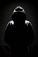 Young person wearing a hoodie sweater and standing in the shadow shadowy background