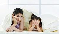 Portrait of mother and daughter under a bed sheet