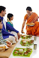 South Indian woman serving food to her family