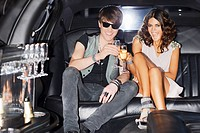 Couple toasting each other in limo