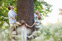 Family standing in circle around tree (thumbnail)
