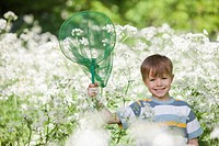 Boy playing with butterfly net in field of flowers