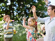 Family playing with bubbles in park