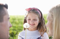 Girl playing with dandelion outdoors