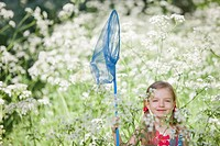Girl playing with butterfly net in field of flowers