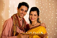 Couple holding a tray with diyas