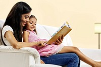 Mother and daughter reading a story book