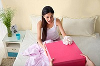 Girl receiving a birthday gift in bed