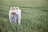 Scientists in protective gear using laptop in field