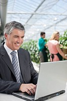 Businessman working on laptop in greenhouse