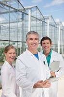 Scientists smiling outside greenhouses