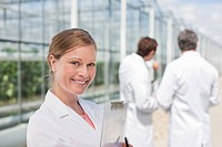 Scientist standing outside greenhouses