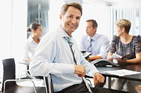 Businessman smiling at conference desk