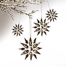Silver snowflakes hanging against pale grey