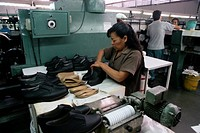 A woman puts inner soles into shoes at the Emyco Shoe Factory.