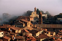 Fog hangs over buildings in the medieval town of Montepulciano in Tuscany, Italy.