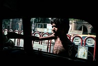 A boy begs for alms through the window of a car. Bombay, India.
