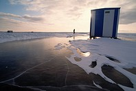 A blue and white ice fishing hut rests on frozen Mille Lacs Lake. Thousands of huts are set up during the fishing season. Mille Lacs, Minnesota, USA.