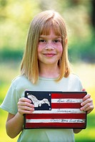 Young girl holding an American flag plaque made in China which reads, God Bless America, Our Home Sweet Home.