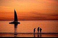 A group of people stand on the shore´s edge as the sunsets over the ocean. A sailboat is cast in silhouette against the sea and sky.