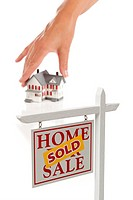 Womans Hand Choosing Home with Sold Real Estate Sign