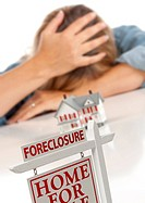 Woman, Head in Hand Behind Model Home and Foreclosure Sign