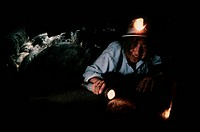 A young spelunker equipped with plenty of lights crawls into the narrow Little Muddy Cave, part of the Lehman Caves complex at Great Basin National Pa...