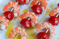 Brochettes of prawns and tomato with olive oil. Spain.