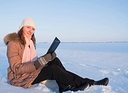 Teen girl reading e_book outdoors at winter time