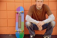 Young Man Kneeling with Skateboard